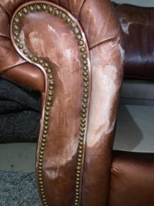 Photo of leather couch arm damaged by mineral deposits
